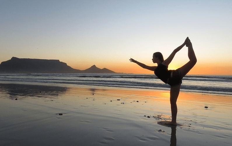 Woman Doing Yoga on the Beach - Unlock Your Health and Lifestyle Universities